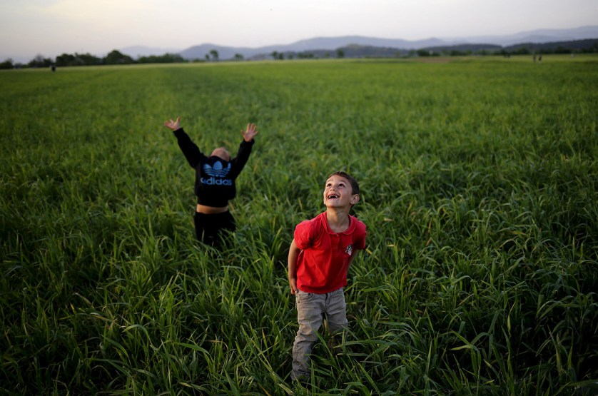 17 April 2016: Children look to the sky as they play with a kite in a field near the Greek-Macedonian border