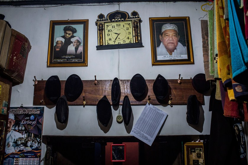 Students skullcaps are seen hanging on the wall with the Lirboyo founder pictures hanging above