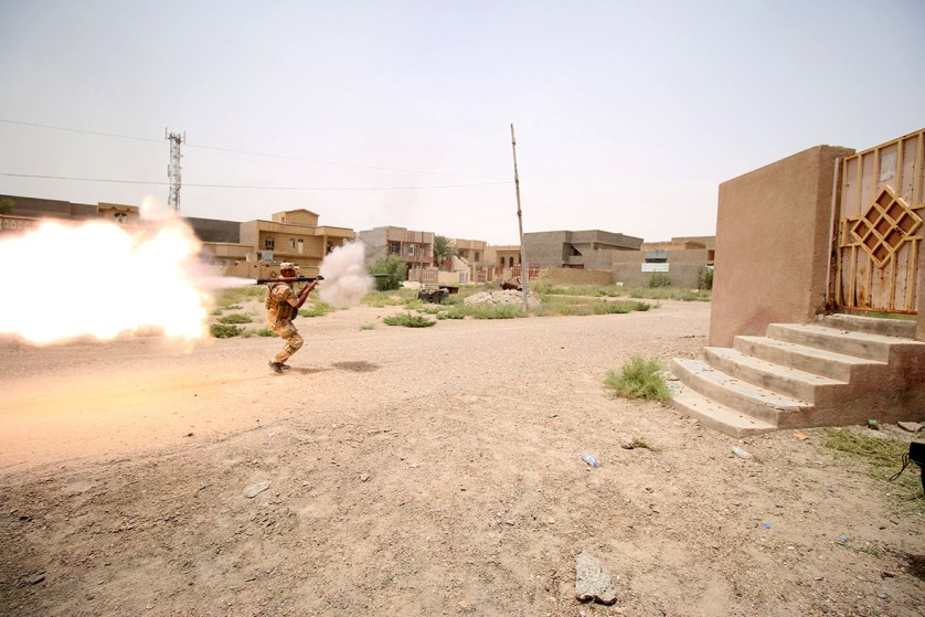A member of the Iraqi pro-government forces fires a rocket-propelled grenade during clashes with Isis fighters as they try to enter the eastern Askari neighbourhood of Fallujah