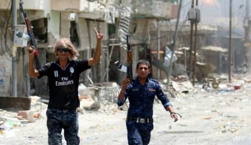 Members of the Iraqi police force celebrate on a street on Jun 27, 2016 in western Fallujah.