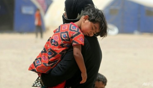 An Iraqi woman displaced from the city of Fallujah carries a child at a newly opened camp where hundreds of Iraqis are taking shelter in Amriyat al-Fallujah on Jun 27, 2016.