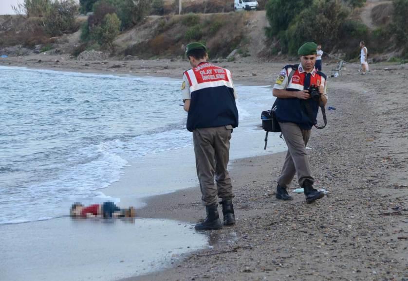 Турецкие полицейские забирают с берега тело утонувшего мальчика, одного из 12 сирийских беженцев, которым так и не удалось добраться до греческого острова Кос