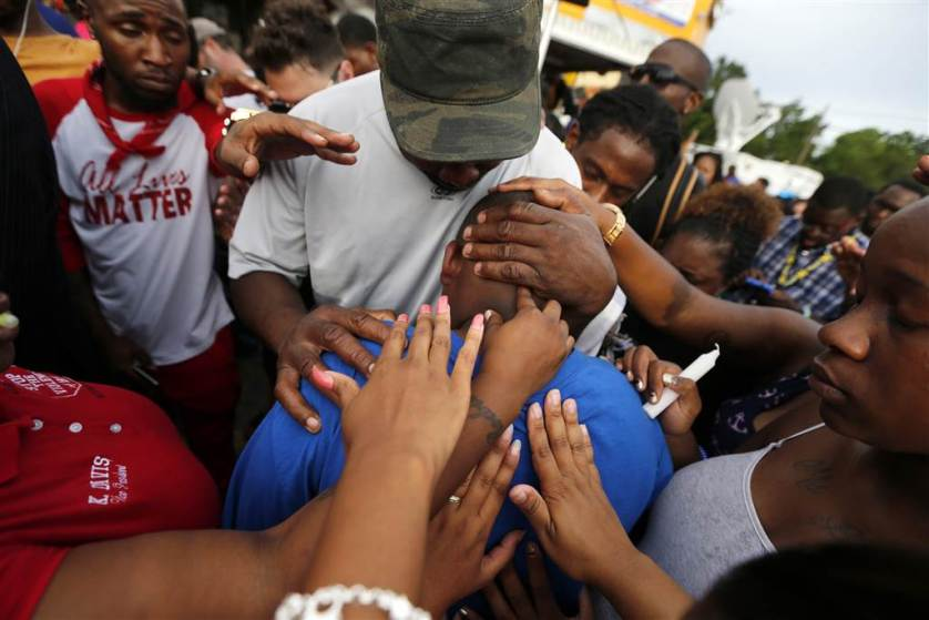 Cameron Sterling, son of Alton Sterling, is comforted by hands from the crowd at a vigil outside the Triple S convenience store in Baton Rouge, Louisiana on July 6. Alton Sterling, 37, was shot and killed by Baton Rouge police outside the store where he was selling CDs.