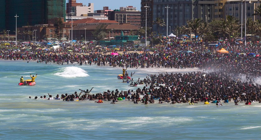 Lifeguards attempt to control the crowd as people visit the beach on new year's day in Durban, South Africa, on 1 January 2014