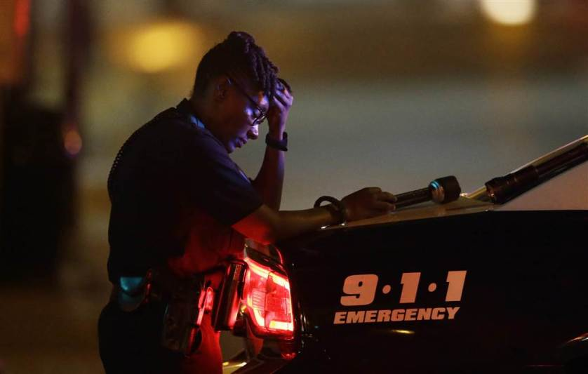 A Dallas police officer takes a moment as she guards an intersection in the early morning after a shooting in downtown Dallas, on July 8. At least two snipers opened fire on police officers during protests in Dallas on Thursday night; some of the officers were killed, police said.