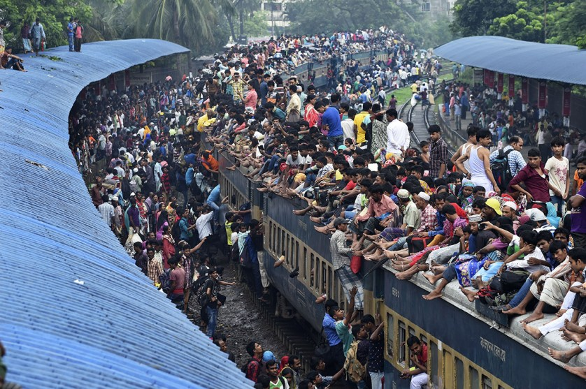 People scramble to reach the roof of an overcrowded train at a station in Dhaka, during the annual festival of Eid al-Adha in 2015