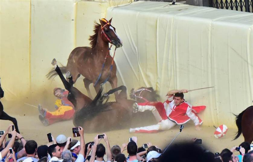 """The jockeys of the """"Contrada of Chiocciola """" and """"Contrada of Giraffa """" fall during the historical Italian horse race of the Palio of Siena on July 2 in Siena."""