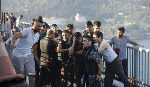 Policemen protect a soldier from the mob after troops involved in the coup surrendered on the Bosphorus Bridge in Istanbul, Turkey July 16, 2016.