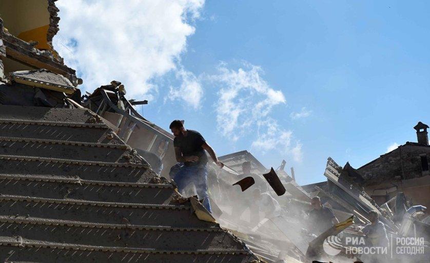 Люди разбирают завалы в городе Аматриче, пострадавшем в результате землетрясения.