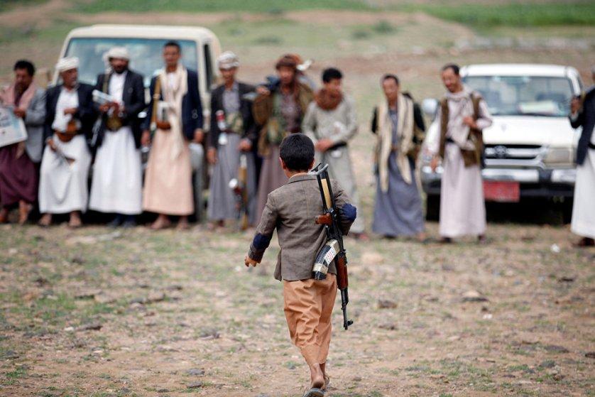 Вооруженный мальчик идет на собрание лояльных по отношению к движению Хути, Йемен.