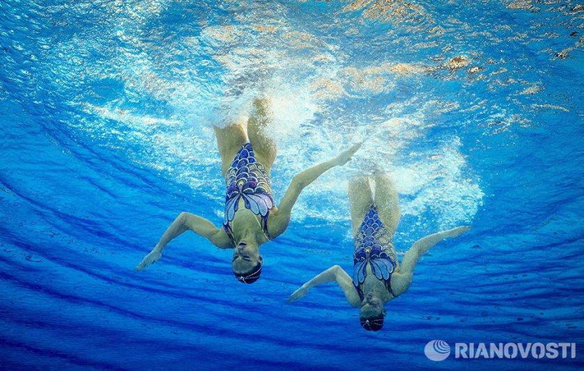 Светлана Ромашина и Наталья Ищенко (Россия) выступают с произвольной программой в соревнованиях по синхронному плаванию среди дуэтов на XXXI летних Олимпийских играх.