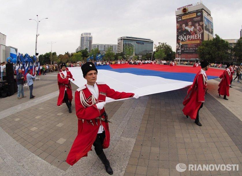 Большой флаг России на театральную площадь Краснодара вынесли представители казачества, военнослужащие и члены Почетного караула Поста №1.