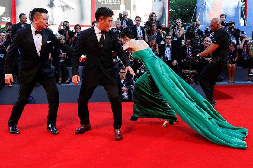 Одна из гостий Венецианского международного кинофестиваля в длинном платье со шлейфом не удержалась на каблуках и упала.