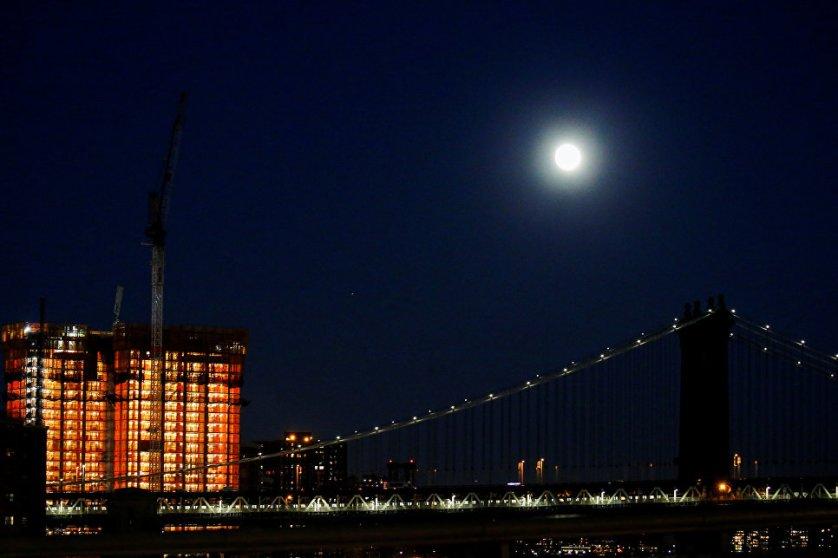 Луна над Манхэттенским мостом накануне суперлуния в Нью-Йорке, США.