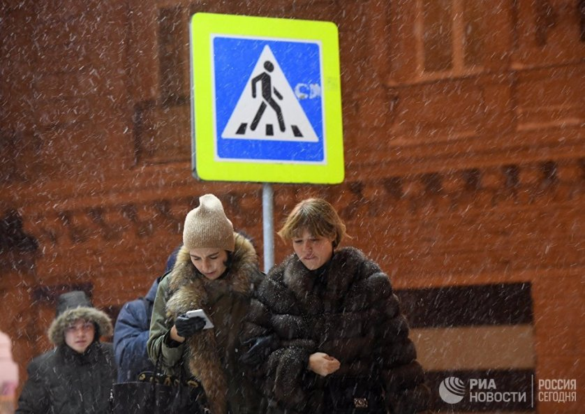 Прохожие в Москве во время снегопада.