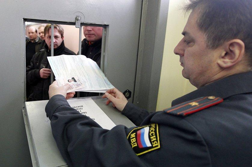 Инспектор ГИБДД принимает документы от водителя на одном из московских пунктов техосмотра автомобилей