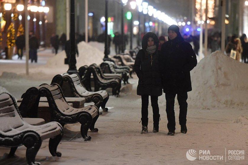 Прохожие в Москве после снегопада.