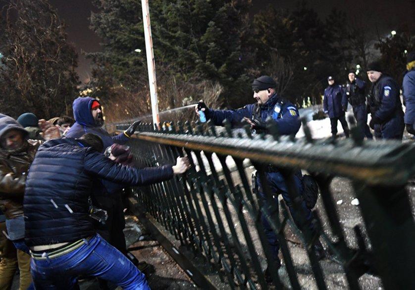 Жандарм применяет против митингующих перцовые баллончики во время акции протеста в Бухаресте.