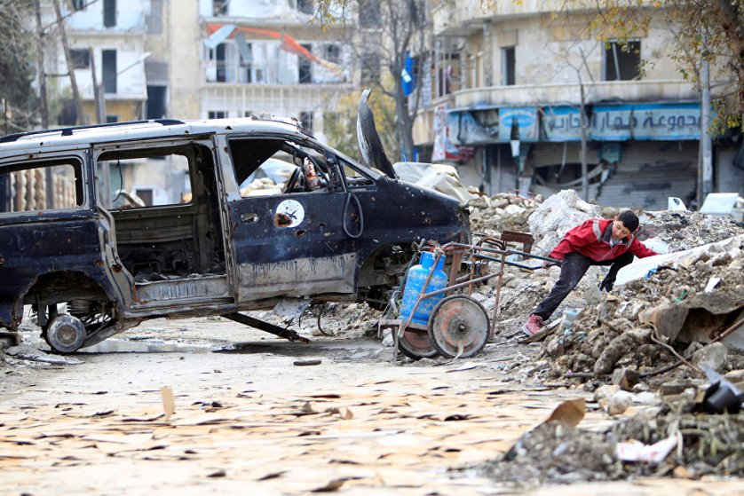 Мальчик везет баллон с газом на одной из разрушенных улиц Алеппо.
