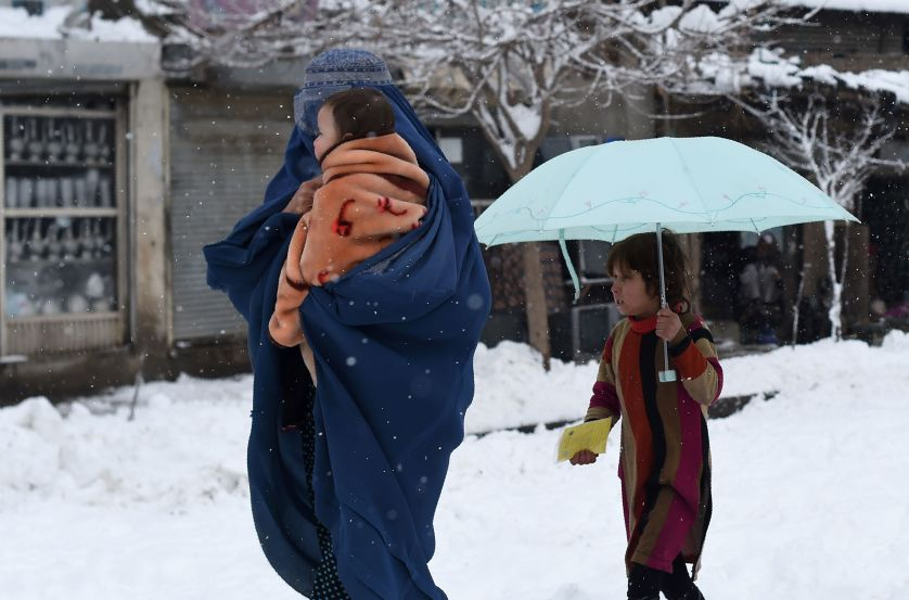 An Afghan clad-burqa woman holds a child as she walks during snowfall in Kabul on February 5, 2017. / AFP / WAKIL KOHSAR