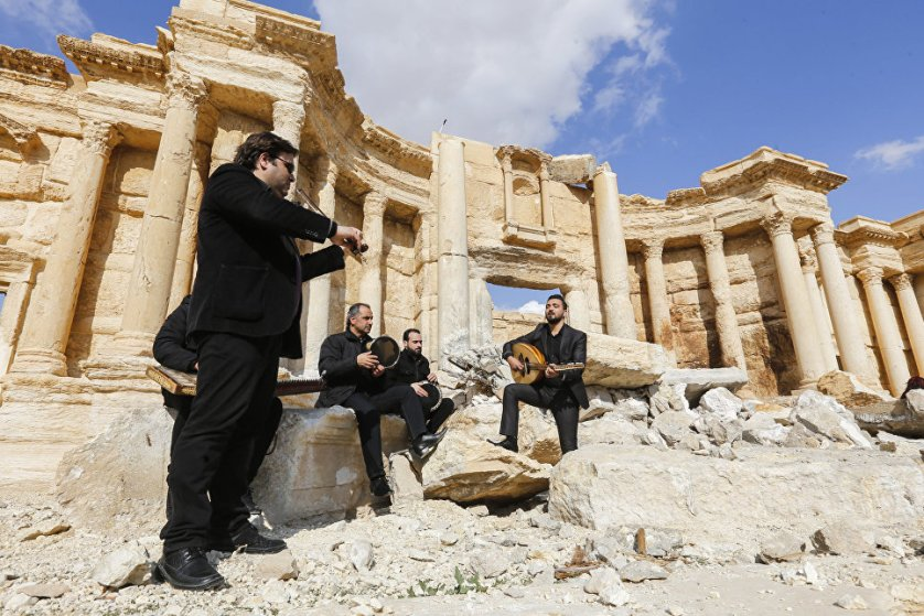 Сирийские музыканты играют на месте разрушенного боевиками римского амфитеатра в древнем городе Пальмира, Сирия.