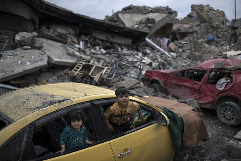 Дети играют в поврежденном автомобиле в освобожденном от террористов районе Мосула, Ирак.