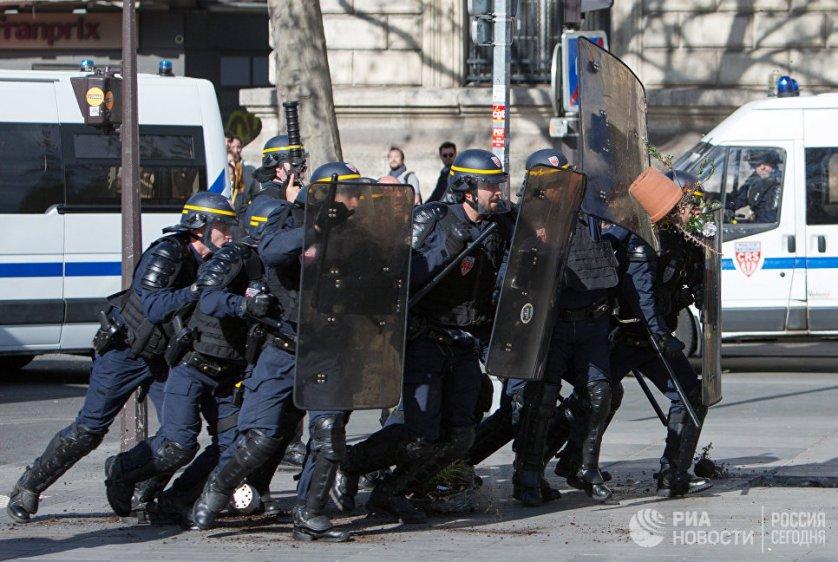 Сотрудники полиции защищаются от протестующих в Париже представителей китайской диаспоры.