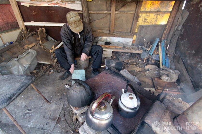 Местный житель следит на улице за печкой, на которой оставшиеся жители дома греют чайники.