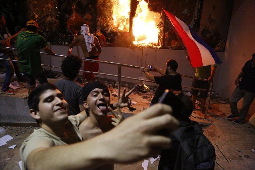 Мужчины фотографируются в Асунсьоне на фоне протестов против принятия поправки в конституцию Парагвая, которая бы позволила выбирать президента на второй срок.