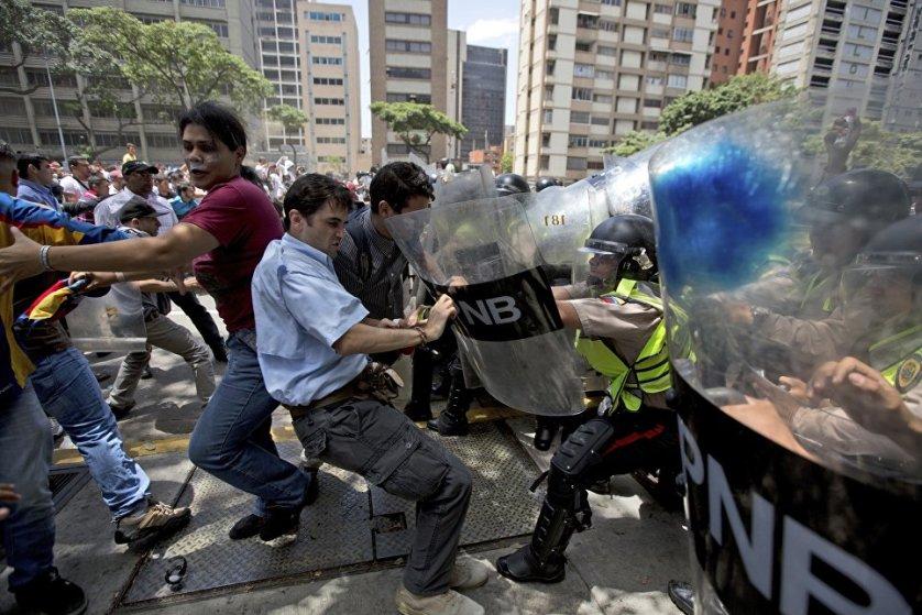 Столкновения демонстрантов с сотрудниками полиции в Каракасе, Венесуэла.