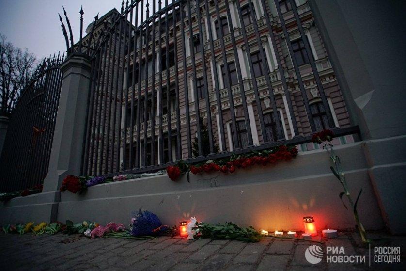 Жители Латвии приносят цветы и зажигают свечи у здания посольства России в Риге.