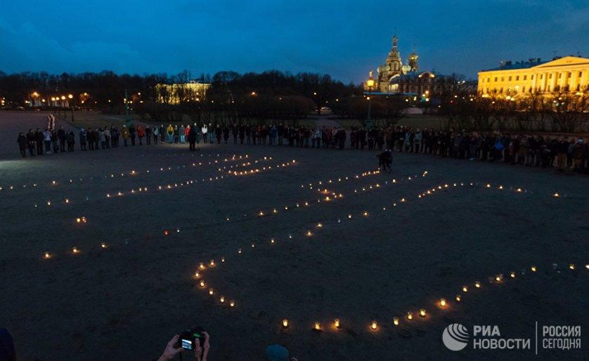 После этого участники акции поставили свечи на землю и встали вокруг горящих цифр.