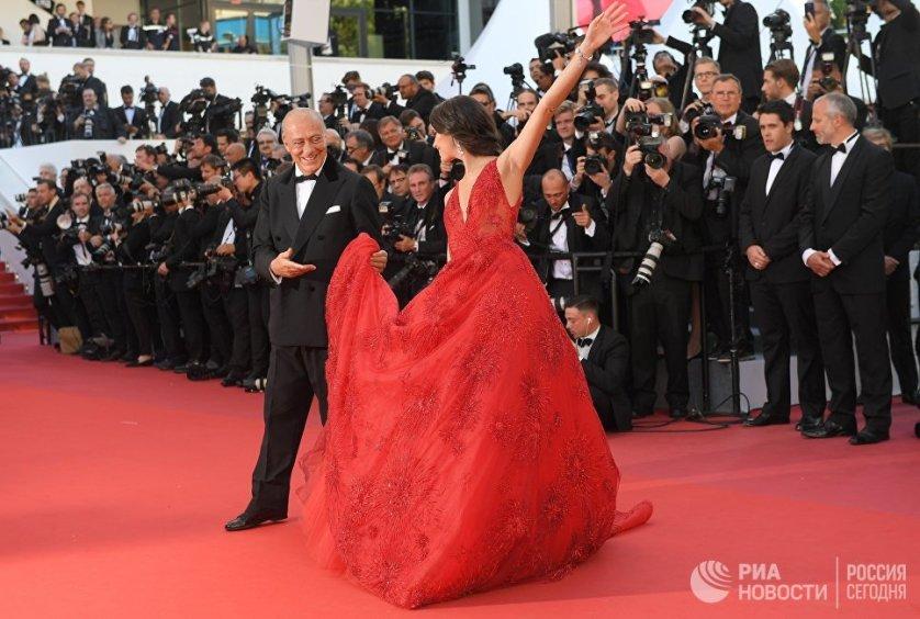 Глава ювелирного дома De Grisogono Фаваз Груози и португальская модель Сара Сампайо. Для дефиле по ковровой дорожке девушка выбрала красное платье с пышной юбкой Zuhair Murad Couture.