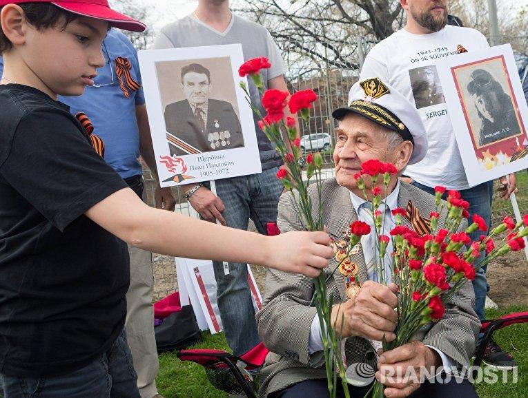 """Традиция дарить ветеранам цветы соблюдалась и на марше """"Бессмертного полка"""" в Монреале, на который пришли сотни человек, в том числе граждане России из США и Канады."""