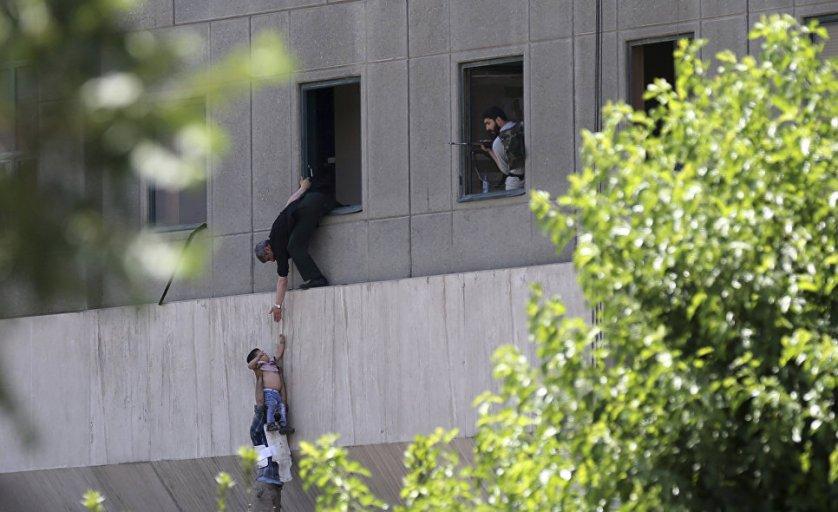 Мужчина из окна передает ребенка охраннику во время нападения террористов на здание иранского парламента в Тегеране.