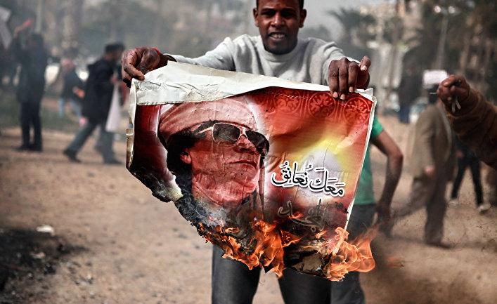 Житель Бенгази сжигает портрет Муамара Каддафи.
