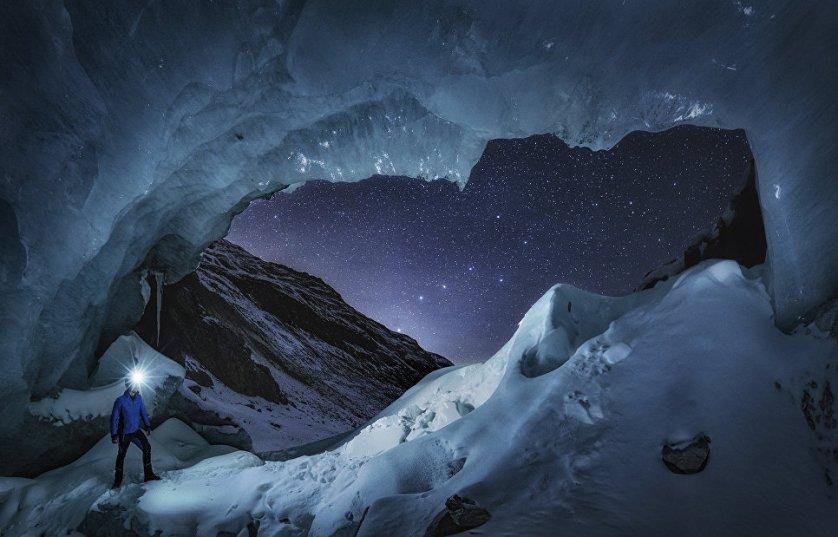 """Работа фотографа Nicholas Roemmelt """"Мисс Большая медведица"""" (Mr. Big Dipper). На снимке - астроном, наблюдающий за звездным небом из входа в большую пещеру на леднике Энгадин, который находится в швейцарском кантоне Граубюнден. Фото сделано наложением кадра звездного неба на передний план ледника."""