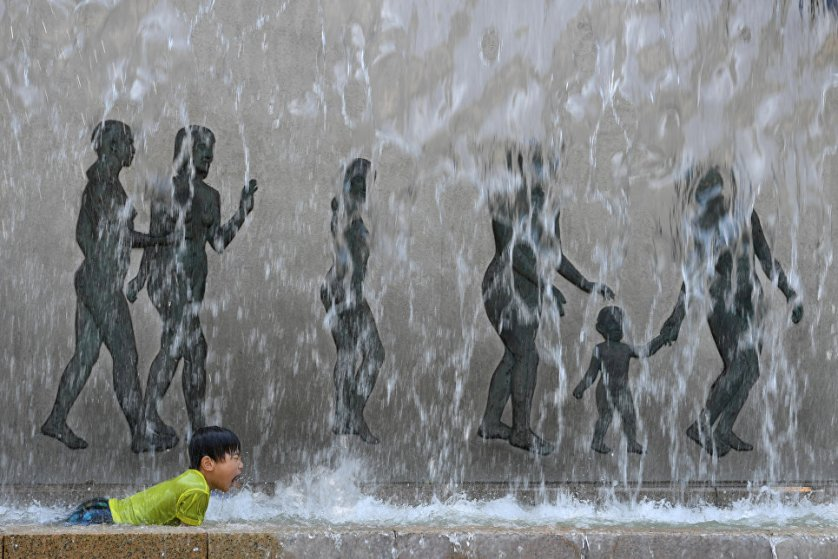 Ребенок во время жары пытается охладиться в одном из фонтанов в Токио.
