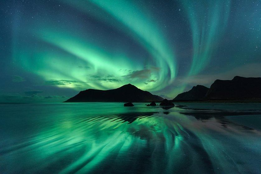 """Работа фотографа Beate Behnke """"Отражения"""" (Reflection). На снимке запечатлено отражение полярного сияния в волновой ряби на пляже Skagsanden, который находится на Лофотенских островах Норвегии."""