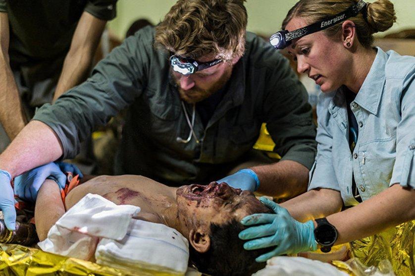 Пит (27, США) и Алекс (США) из Академии реагирования на чрезвычайные ситуации осматривают ребенка, пострадавшего от авианалета, во время которого погибли его родители, а двое братьев были ранены.