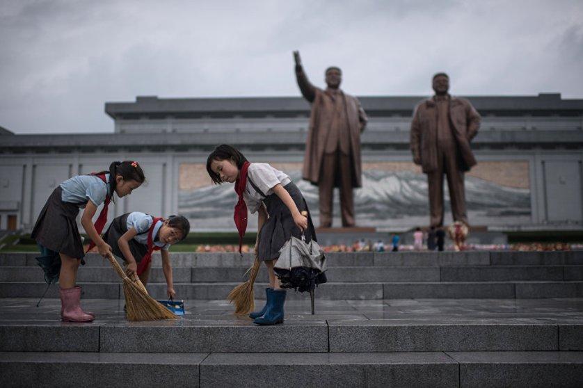 Пионеры подметают ступеньки возле статуй Ким Ир Сена и Ким Чен Ира в Пхеньяне.