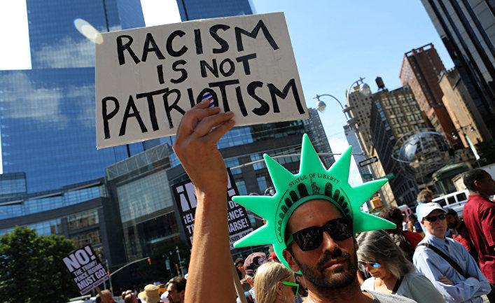 13 августа 2017. Акция протеста против белых националистов в Нью-Йорке. Надпись: «Расизм это не патриотизм».