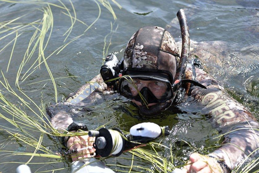 """Путин также занимался рыбалкой и подводной охотой, плавая в гидрокостюме. На маске установили камеру GoPro. Благодаря ей удалось запечатлеть уникальные кадры его двухчасовой """"охоты на щук"""". На фото: Владимир Путин во время подводной охоты в гидрокостюме на каскаде горных озер в Республике Тыва."""