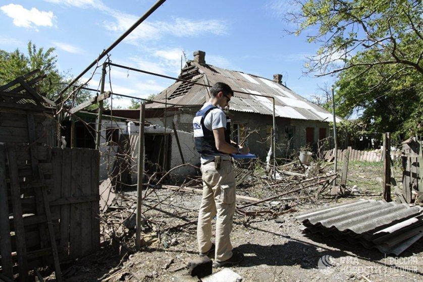 Сотрудник ОБСЕ осматривает двор жилого дома, пострадавший в результате обстрела Докучаевска в Донецкой области