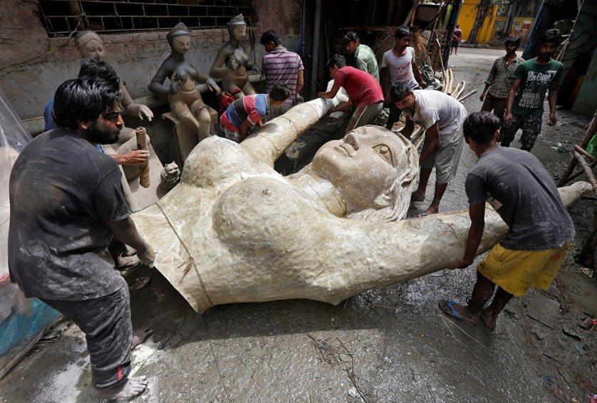 Ремесленники несут женскую скульптуру из стекловолокна, созданную для индуистского фестиваля Дурга-пуджа в Калькутте.