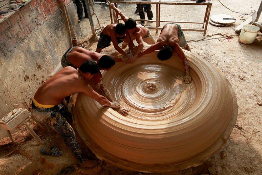 Рабочие лепят фарфоровый чан на заводе в Китае.