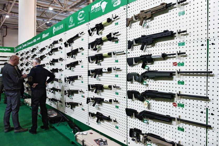 Посетители у стенда производителей огнестрельного оружия.
