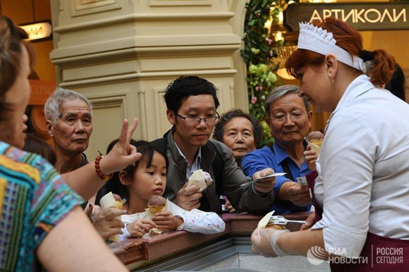 Туристы покупают мороженое в ГУМе в Москве