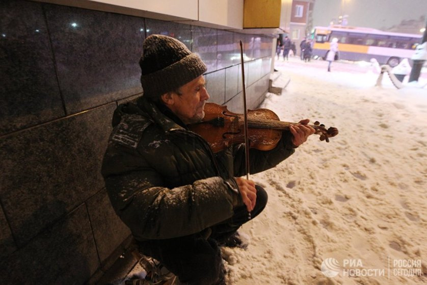 Мужчина играет на скрипке на улице во время снегопада во Владивостоке