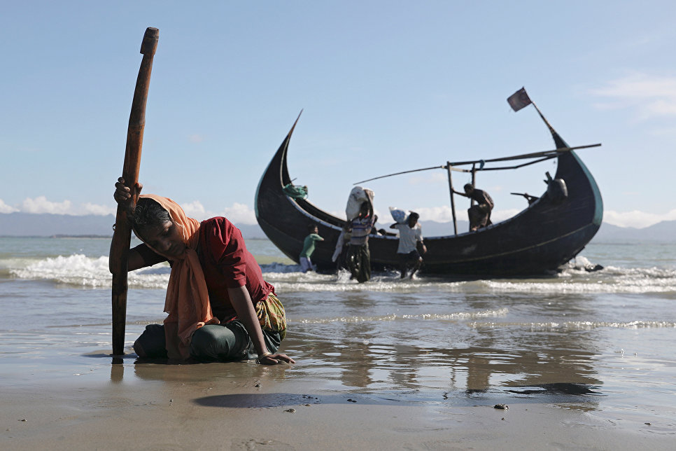 Беженка рохинджа упала без сил после высадки на берегу города Текнаф, Бангладеш.